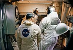Technicians in the white room atop Pad A prepare to insert astronauts.jpg