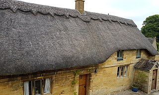Thatched roof with a block ridge in the UK; the wheat reed material is common in the Cotswolds