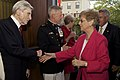 The Commandant of the U.S. Marine Corps Gen. James F. Amos, center, and the Evening Parade guest of honor, John Warner, left, a former secretary of the Navy and U.S. senator, greet a guest during a reception 130503-M-LU710-054.jpg