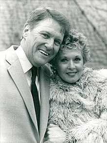 A black-and-white photo of two middle-aged Caucasians; a man and woman. The man with short, light-colored hair, wears a light-colored suit with a dark tie, and is smiling towards the camera. The woman, who also has short, light-colored hair, wears a fur coat, and is also looking towards the camera with a smile.