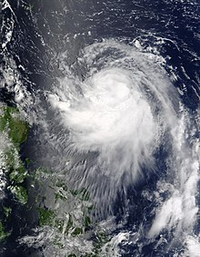 Image of a tropical cyclone to the right of a group of small landmasses. The tropical cyclone is characterized by a sprawling mass of spiralingclouds, though no eye is evident.