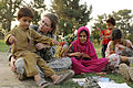 U.S. Air Force Capt. Mary Danner-Jones, a public affairs officer with the Nangarhar Provincial Reconstruction Team, teaches an Afghan boy and his sisters to make friendship bracelets during a Girl Scout meeting 100821-F-FW394-142.jpg