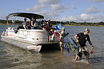 U.S. Air Force Maj. Clint Schulz, of the 559th Flying Training Squadron out of Randolph Air Force Base, Texas, carries equipment and supplies off a boat ferrying volunteers supporting Operation Float a Soldier 100821-F-SS509-004.jpg
