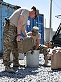 U.S. Army Sgt. 1st Class Dustin Austin, left, with Combined Joint Interagency Task Force 435, adds water to a mixture to make fuel donuts for an Operation Outreach Afghanistan program at Camp Phoenix, Kabul 130728-F-JL359-007.jpg