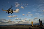 U.S. Navy Boatswain's Mate 2nd Class Cassandra Collier signals to a French Army SA 380 Puma helicopter as it takes off from the amphibious dock landing ship USS Pearl Harbor (LSD 52) while underway in 130628-N-WD757-271.jpg