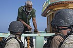 U.S. Sailors assigned to the guided missile destroyer USS Mason (DDG 87) assist a fisherman aboard a dhow during a visit, board, search and seizure operation Nov. 23, 2013, in the Gulf of Aden 131123-N-PW661-015.jpg
