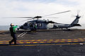 U.S. Sailors prepare an MH-60S Seahawk helicopter assigned to Helicopter Sea Combat Squadron (HSC) 4 for takeoff from the flight deck of the aircraft carrier USS Ronald Reagan (CVN 76) May 3, 2013, while 130503-N-HT107-019.jpg