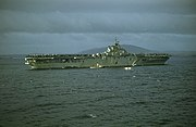 A color photo of an aircraft carrier at sea from a distance