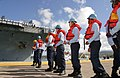 US Navy 030426-N-3228G-017 Naval Station Pearl Harbor line-handlers help moor the aircraft carrier USS Abraham Lincoln (CVN 72) for a brief one-day liberty port after the ship's 10-month deployment in support of Operation.jpg