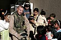 US Navy 061128-M-8213R-023 Master Sgt. Allen, assigned to the 4th Civil Affairs Group (4th CAG), entertains children as Iraqi women speak with female Marines attached to the 4th CAG.jpg