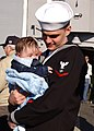 US Navy 070131-N-8544C-036 Electronics Technician 3rd Class Lee Medlin embraces his three-month-old son at the homecoming ceremony for guided missile frigate USS Boone (FFG 28).jpg