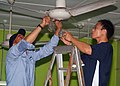 US Navy 070719-N-0120A-042 Dock landing ship USS Harpers Ferry (LSD 49) Sailor and a Singapore navy sailor work together cleaning fans at a Movement for the Intellectually Disabled of Singapore (MINDS) training and development.jpg