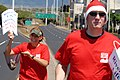 US Navy 070725-N-4965F-003 Personnel Specialist 1st Class Robert Whittle and Master-at-Arms 1st Class Jinine Green spread Christmas cheer to passing motorists as part of a volunteer project and fundraiser for the River of Life.jpg
