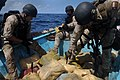 US Navy 091015-N-4154B-303 Members of a visit, board, search and seizure team from the guided-missile cruiser USS Anzio (CG 68) and U.S. Coast Guard Maritime Safety and Security Team 91104 dispose of bags of illegal narcotics.jpg