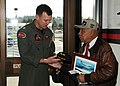 US Navy 100116-N-9860Y-003 Cmdr. Mark Hamilton, commanding officer of the Grey Knights of Patrol Squadron (VP) 46, presents a command photo and ball cap to retired U.S. Air Force Lt. Col. William Holloman III.jpg