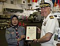 US Navy 110123-N-7981E-194 Capt. Bruce Lindsey accepts a certificate of appreciation from headmistress Nik Nab and scouts from SK Taman Tun Dr. Ism.jpg