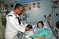 US Navy 110927-N-AU127-629 Aviation Electrician's Mate 2nd Class Anthony Barnardo, assigned to USS Constitution, gives a Navy ball cap to a patient.jpg