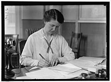A portrait of Van Kleeck at work at a busy desk with the Russell Sage Foundation before WWI