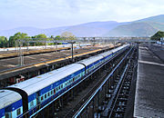 Outdoor train station, with long passenger train