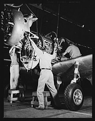 Vultee Aircraft - Hanging an engine on a BT-13 Valiant trainer at the Vultee aircraft plant, Downey, California in World War II.