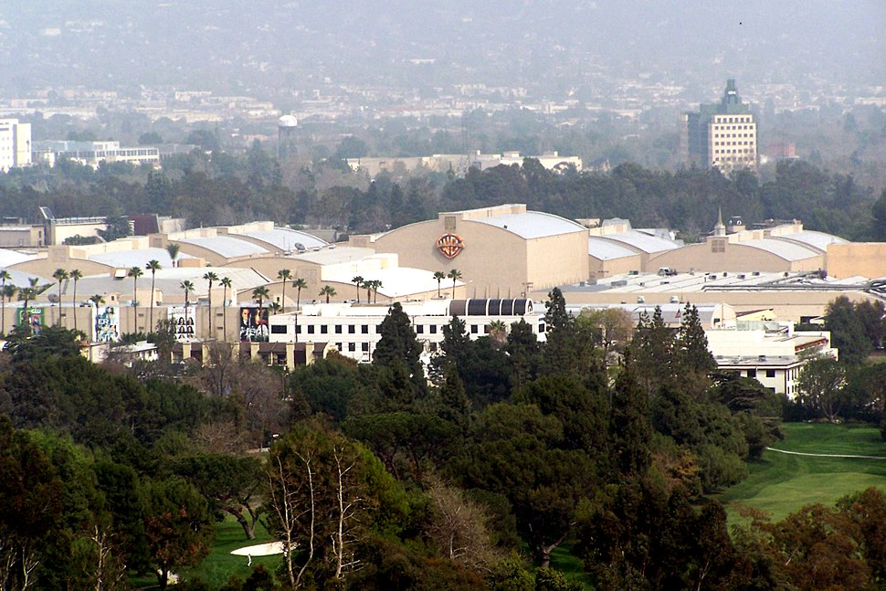 A photograph of a large set of buildings, behind several trees and a hill.