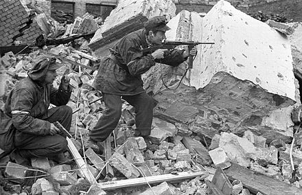 "Home Army soldiers Henryk Ozarek ""Henio"" (left) holding a Vis pistol and Tadeusz Przybyszewski ""Roma"" (right) firing a Blyskawica submachine gun, from ""Anna"" Company of the ""Gustaw"" Battalion fighting on Kredytowa-Krolewska Street, 3 October 1944; the use of pistols in street battles indicates a very poor equipment of weapons of the rebels Warsaw Uprising by Chrzanowski - Henio Roma - 14828.jpg"