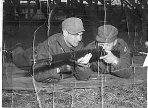 Whitey Ford - Whitey Ford (right) Shooting a rifle in training for the military.