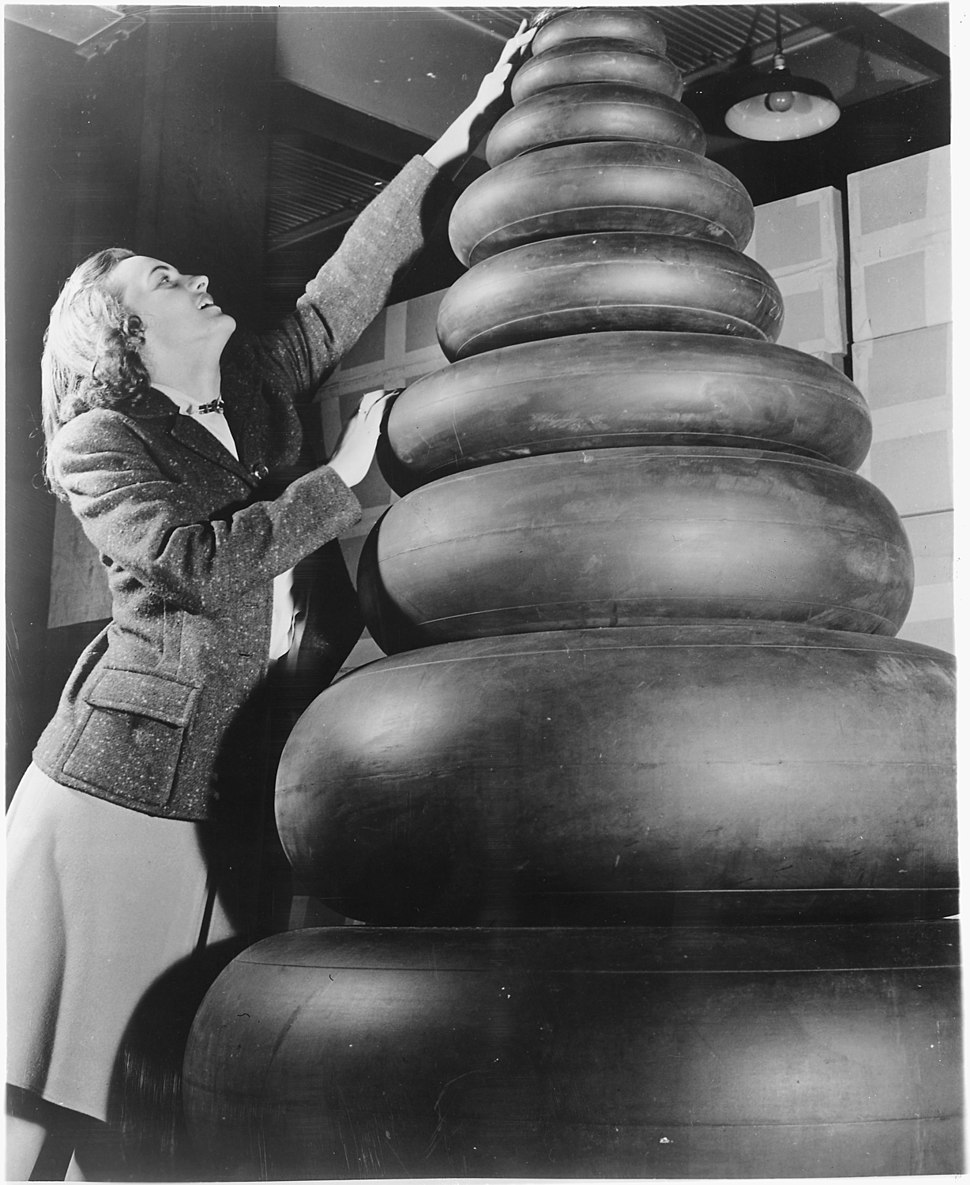 Woman standing next to a wide range of tire sizes required by military aircraft. - NARA - 196199