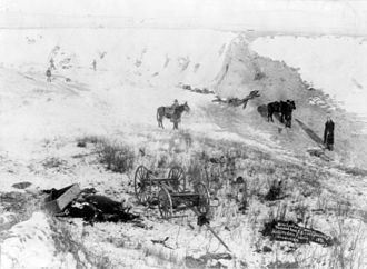 Timeline of South Dakota - View of canyon at Wounded Knee, dead horses and Lakota bodies are visible.