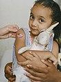 Young girl holding stuffed animal having band-aid applied (48546119217).jpg