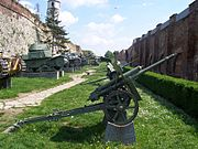 a small green-painted wheeled artillery piece with a split trail mounted on a concrete plinth