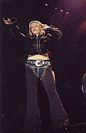 A female standing on a stage. She has short blond hair and wears black jeans and a jacket. Her right hand points a vocal microphone toward the audience, to pick up their sound. Her left hand is held behind her ear with a facial expression indicating that she is listening.