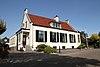 foto van Raiffeisenbank. Witgepleisterd laag huis met rechte kroonlijst