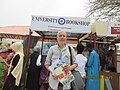 "ASC Leiden - van de Bruinhorst Collection - Somaliland 2019 - 4708 - The photographer, holding a children's book ""Irbaddii luntay. Axmed Cabdillahi Cawaale"" (Ahmed Awaleh) in front of a book stall of the University Bookshop, Somaliland.jpg"