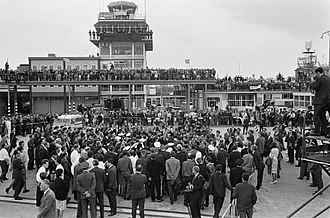 British Invasion - Fans and media swarm the Beatles at Schiphol Airport in 1964.