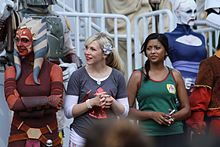two female actresses with people in costumes around