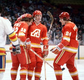 Calgary Flames - Tom Lysiak celebrates with teammates after a goal against the Colorado Rockies. From 1972 to 1980 the Flames were based in Atlanta.