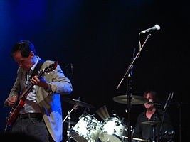 Prominent in the foreground, a guitarist concentrates on his playing, while the drummer, a little behind him to his left, toils away.