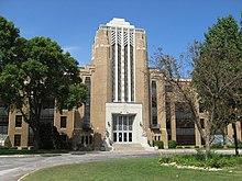 brown and white multi-story building, Art Deco style, with stone statues on each side of the steps, a circular drive in front, and green trees on the sides and center island of the drive