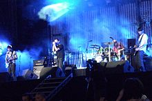 Four men perform on a stage, which is lit with blue light. One sings into a microphone, another plays drums and the other two play guitars as a crowd watches.