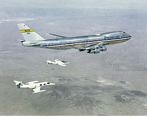 Chase plane - Two chase aircraft, a Learjet and a Cessna T-37, in formation with a NASA Boeing 747.
