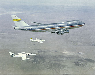 Chase plane - Two chase aircraft, a Learjet and a Cessna T-37, in formation with a NASA Boeing 747 905 as part of a wing vortex experiment.