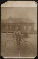 Boy standing next to a bicycle, house in the background LCCN2015652133.tif