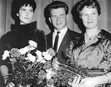 A man in a suit stands in the middle of two formally dressed women, each holding a flower bouquet.