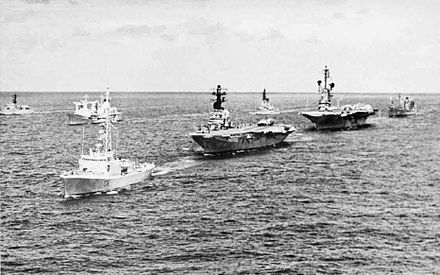 Warships sailing in a line on the open ocean. A small warship leads the line, followed by two aircraft carriers and a replenishment vessel. Other warships sailing in the same direction are in the background.