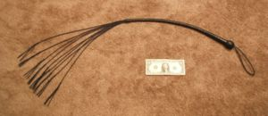 A leather cat o' nine tails pictured with a U....