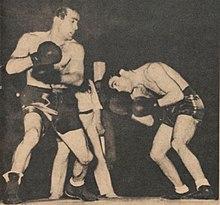 Deux boxeurs face à face. L'un a la tête baissée et l'autre vient de frapper dans le vide.