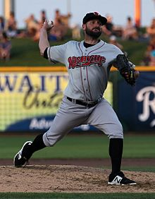 "A man in a gray baseball uniform with ""Nashville"" written on the chest in red, high black socks, a black cap having just pitched a ball from the pitcher's mound"