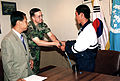 Col. Donald Kropp, United Nations Command Military Armistice Commission (UNCMAC), greets Sgt. Dong In Sop, a North Korean defector, upon his arrival at UNCMAC Headquarters on the Yongsan Army Garrison 990916-A-AX877-002.jpg