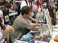 Comic-Con 2006 - Joss Whedon signs at the Browncoats booth (4798033935).jpg